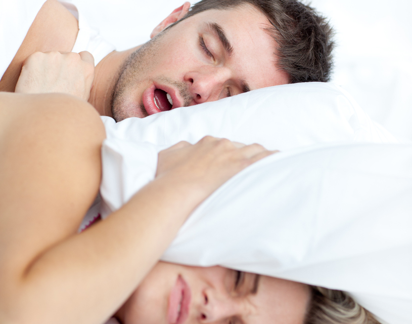 Couple in bed - man snoring, woman with pillow on her head!